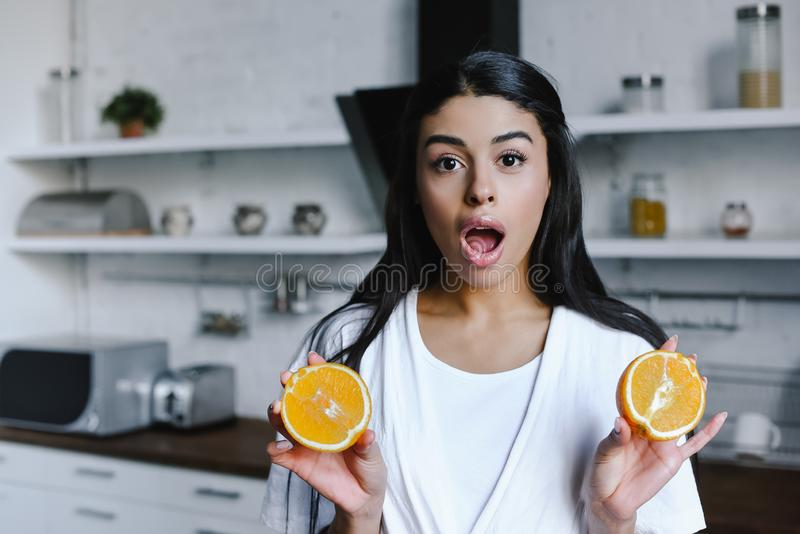 Shocked mixed race girl in white robe holding cut orange and looking at camera in morning. In kitchen royalty free stock images