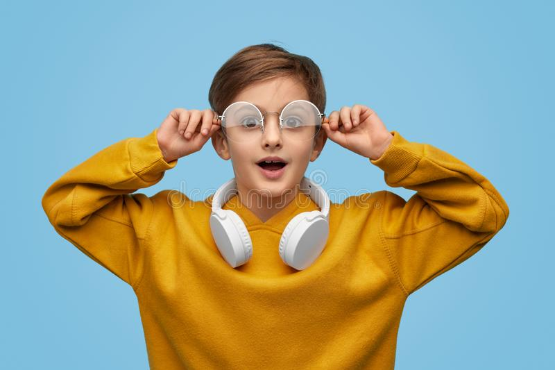 Shocked nerd looking at camera. Astonished boy adjusting stylish glasses and looking at camera against blue background royalty free stock photos