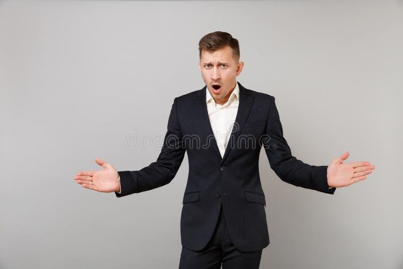 Shocked a outragé le jeune homme d'affaires dans le costume noir classique, mains de propagation de chemise, maintenant grand ouv photographie stock libre de droits