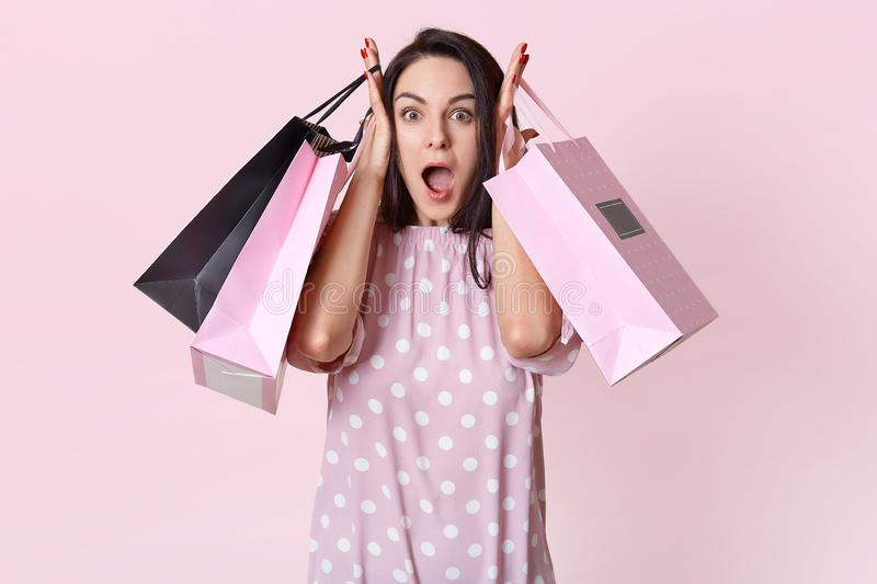 Shocked overwhelmed young pretty woman keeps jaw dropped, has no money for buying expensive thing, holds bags, goes shopping on stock photography