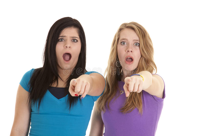 Shocked point teens. Two teen girls with shocked expressions on their faces pointing their fingers at the camera royalty free stock photos