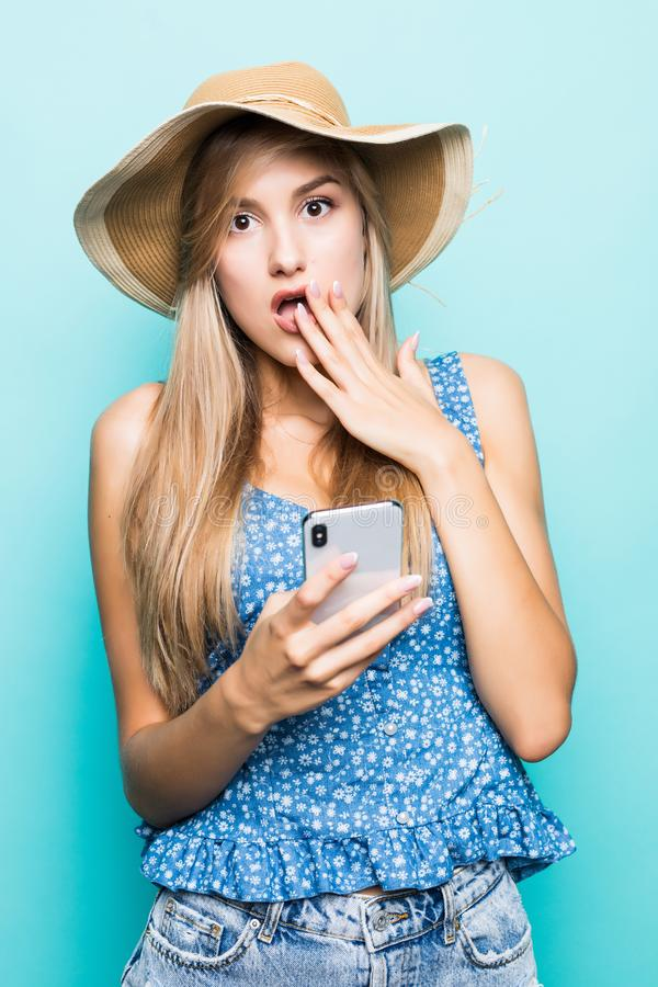 Shocked woman in dress and straw hat quarrels by smartphone while looking away over blue background. Shocked Pretty brunette woman in dress and straw hat royalty free stock images