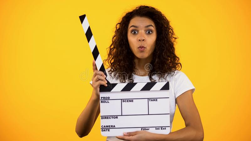 Shocked producer assistant holding clapper board, shooting movie film production. Stock photo stock image