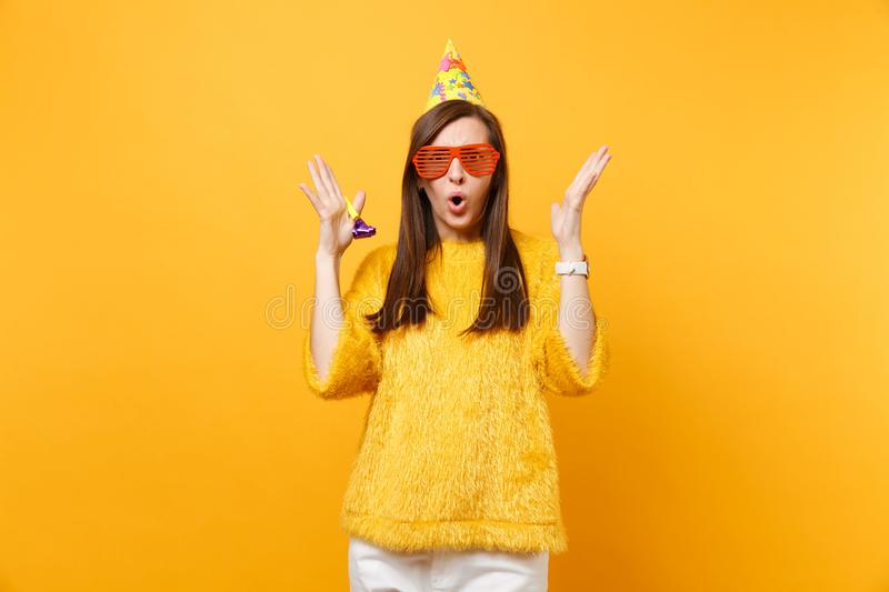 Shocked puzzled woman in orange funny glasses, birthday hat with playing pipe spreading hands, celebrating isolated on royalty free stock photo