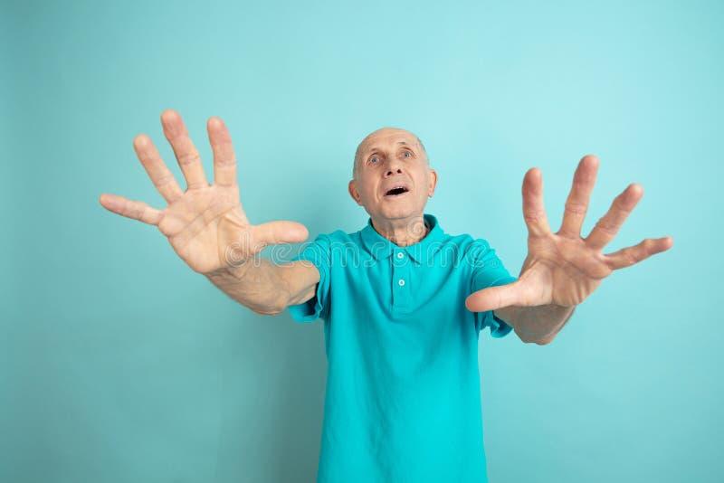 Caucasian senior man`s portrait isolated on blue studio background royalty free stock photos