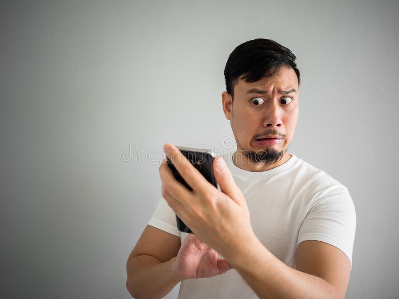 Shocked and scary face of man get yelled from smartphone.  See s. Shocked and scary face of Asian man get yelled from smartphone.  See something scary in royalty free stock images