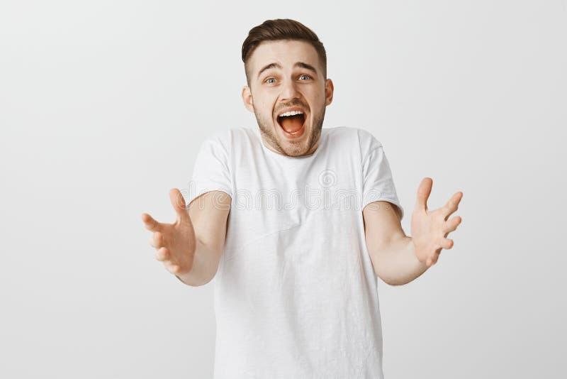 Shocked se preocupó e individuo triste con la barba que tiraba de las manos hacia cámara que encogía y que gritaba de pesar que e imágenes de archivo libres de regalías