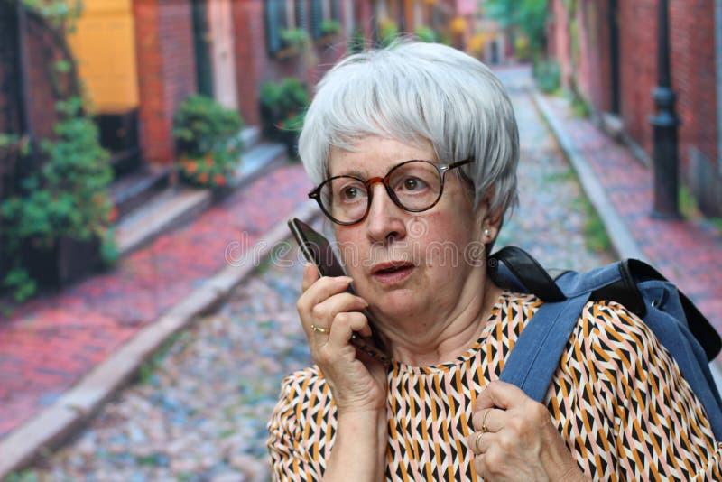Shocked senior woman calling outdoors stock photos