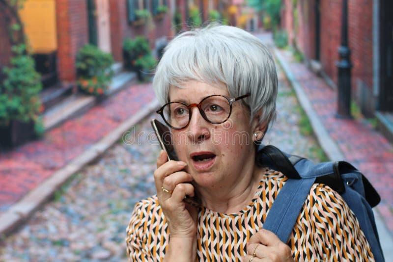 Shocked senior woman calling outdoors royalty free stock photos