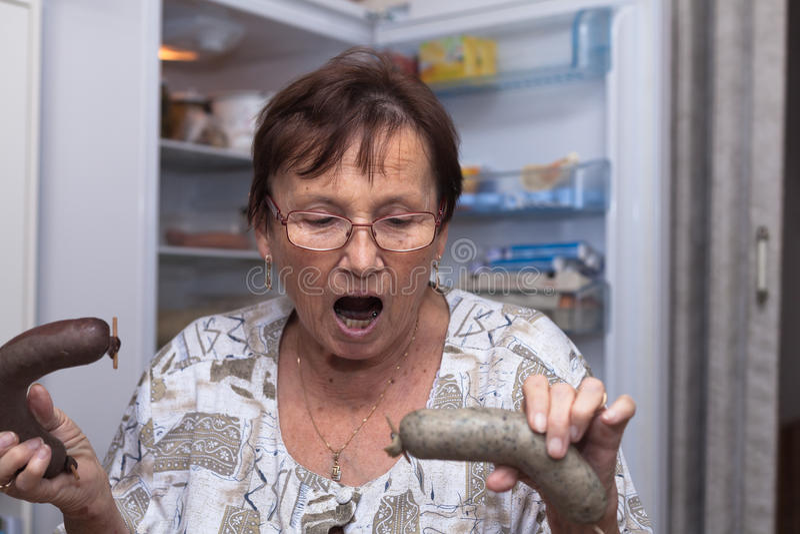 Shocked senior woman holding pork liver sausages stock photography