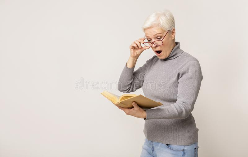Shocked senior woman reading book and taking off glasses in amazement stock images