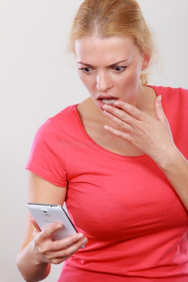 Shocked sorgte sich die Frau, die Telefon betrachtet stockfoto