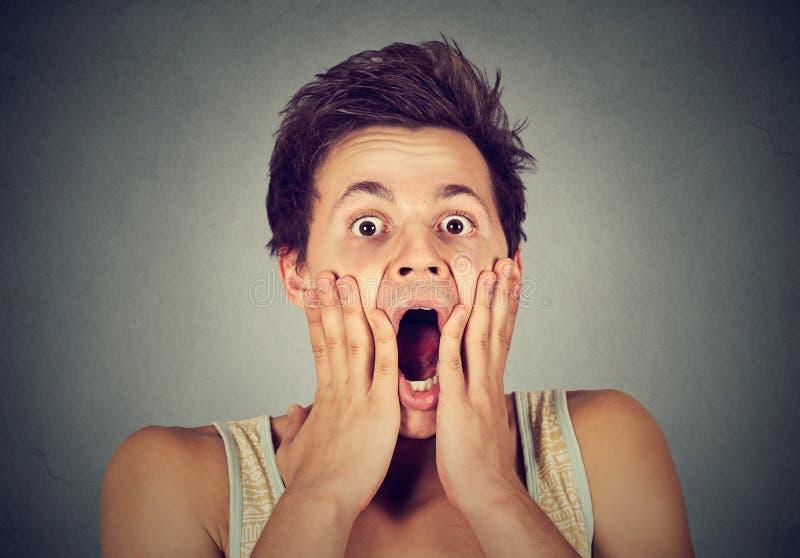 Shocked sorprendió al hombre con las manos en cara que gritaba imágenes de archivo libres de regalías