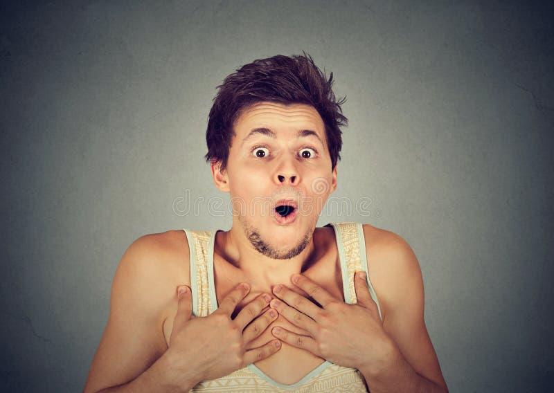 Shocked sorprendió al hombre en incredulidad completa con las manos en pecho fotografía de archivo