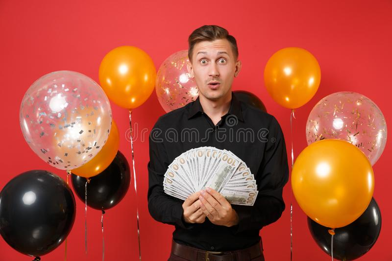 Shocked sorprendió al hombre joven en porciones clásicas del paquete de la tenencia de la camisa de dólares, dinero del efectivo  fotografía de archivo libre de regalías