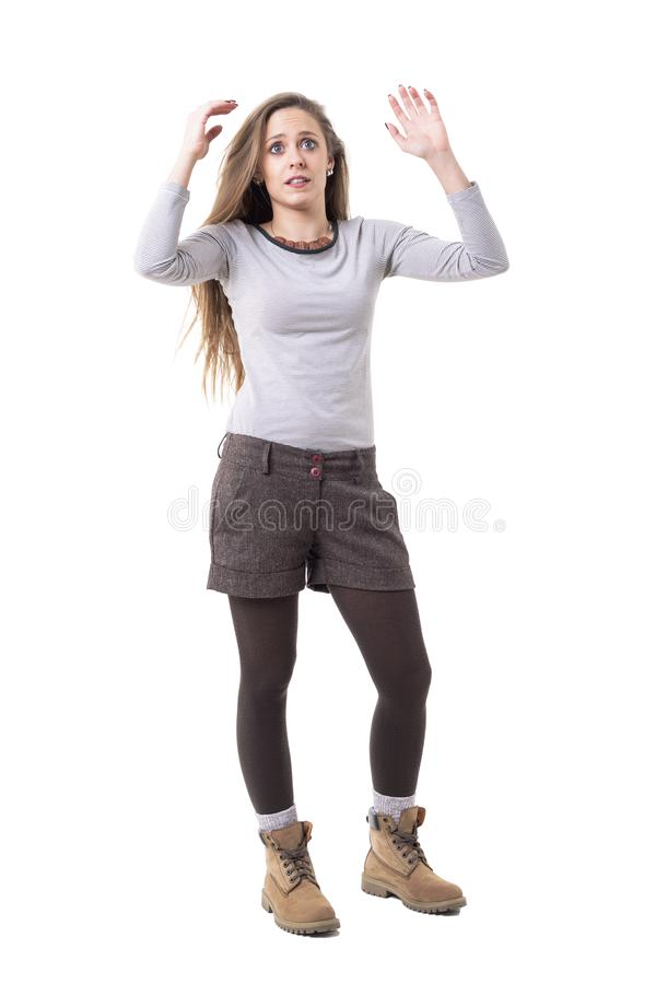Shocked startled young pretty expressive hipster woman looking up with arms raised up. stock images