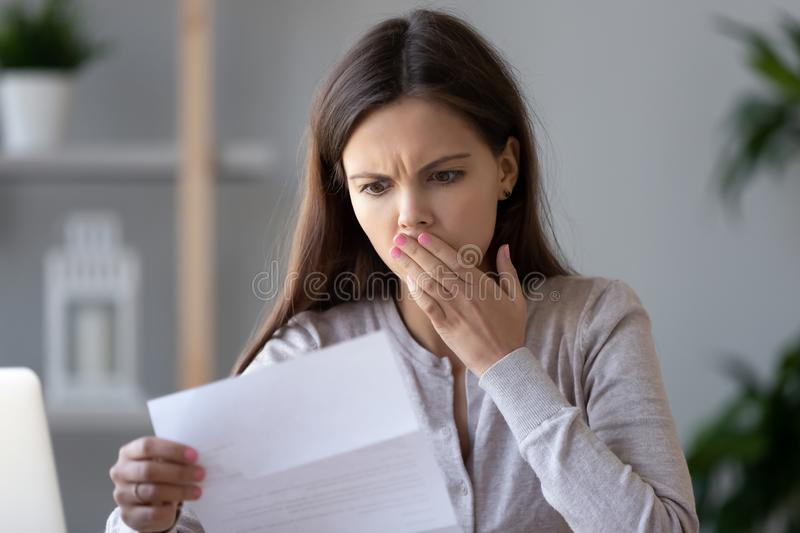 Shocked stressed young woman reading document letter about debt. Shocked stressed young woman reading document letter from bank about loan debt financial problem stock photos