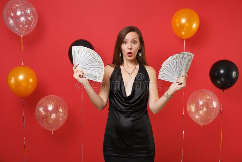 Shocked a stupéfié la jeune femme dans peu de célébration noire de robe, tenant un bon nombre de paquet de dollars, argent d'arge photo libre de droits