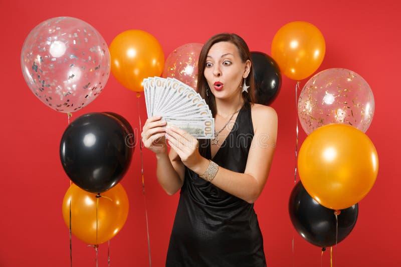 Shocked a stupéfié la jeune fille dans la robe noire regardant sur un bon nombre de paquet de dollars encaissent l'argent dans de images stock