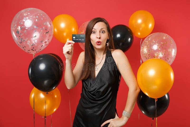 Shocked surpreendeu a jovem mulher em pouco vestido preto que comemora e que guarda o cartão de crédito no ar vermelho brilhante  fotos de stock royalty free