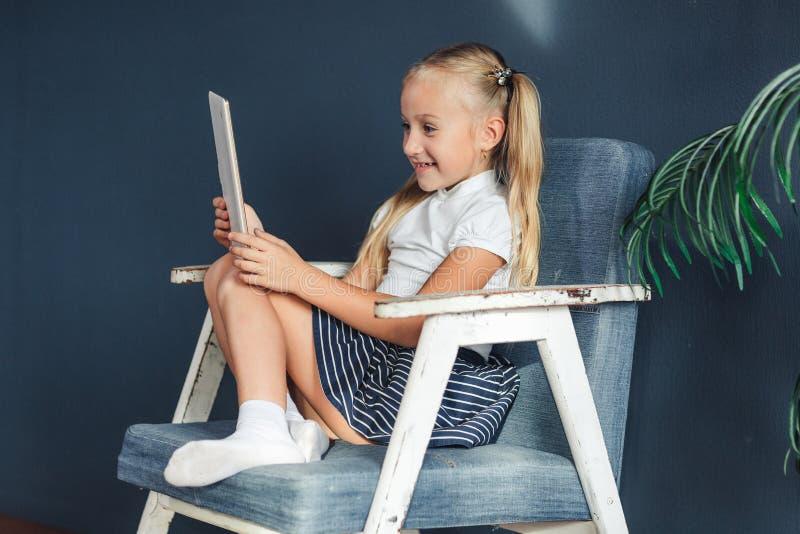 Shocked surpreendeu a menina pre adolescente que joga no PC da tabuleta aberto sua boca na sala de visitas em casa conceito da at fotos de stock royalty free
