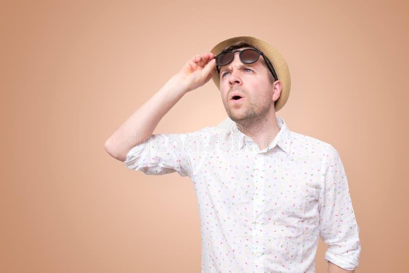 Shocked surpreendeu o homem no chap?u do ver?o que toca em seus vidros imagem de stock royalty free