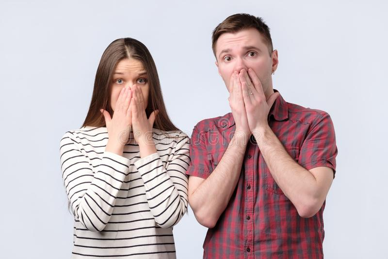 Shocked surpreendeu os pares novos que cobrem a boca com as mãos que olham a câmera fotos de stock