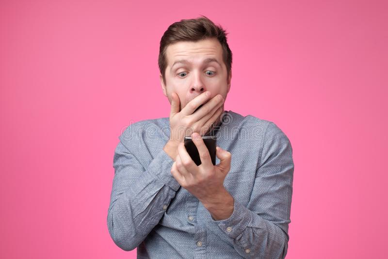 Shocked and surprised european man reading sms on smartphone. And closing his mouth with hand stock photos