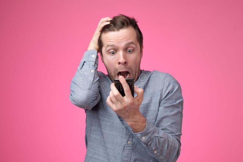 Shocked and surprised european man reading sms on smartphone. Looking with fear royalty free stock photo