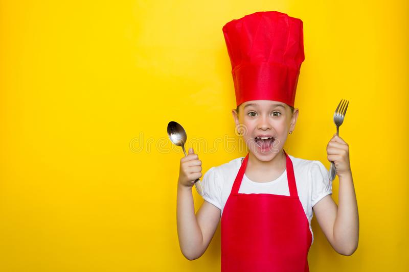 Shocked and surprised girl screaming in a red chef`s suit holding a spoon and fork on yellow background with copy space stock images