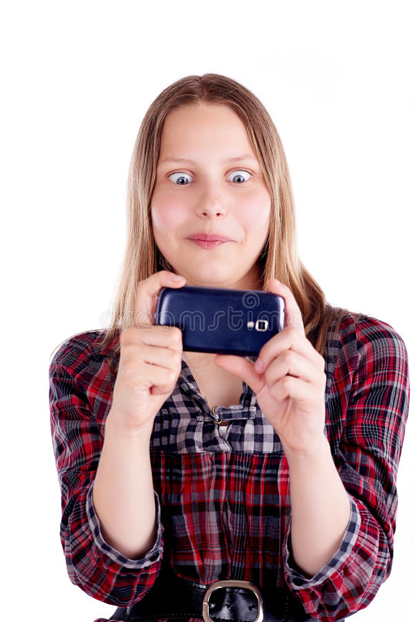 Shocked teen girl looking at mobile phone screen royalty free stock image