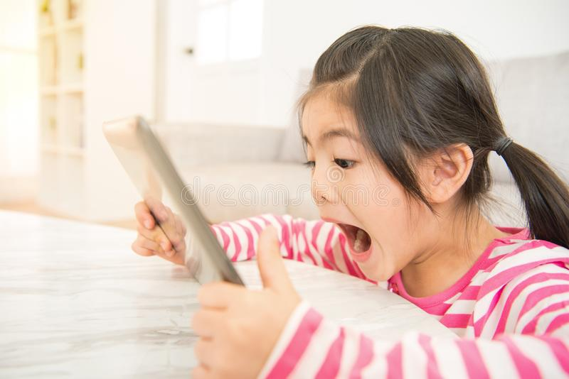 Shocked teen girl playing on tablet pc royalty free stock photography