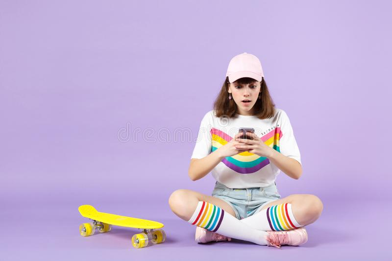 Shocked teen girl in vivid clothes sitting near skateboard, using mobile phone, typing sms message isolated on violet royalty free stock photography
