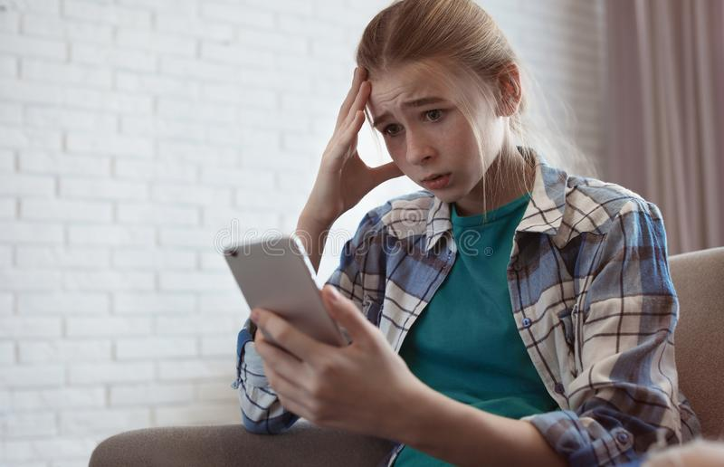 Shocked teenage girl with smartphone indoors. Danger of internet royalty free stock photography