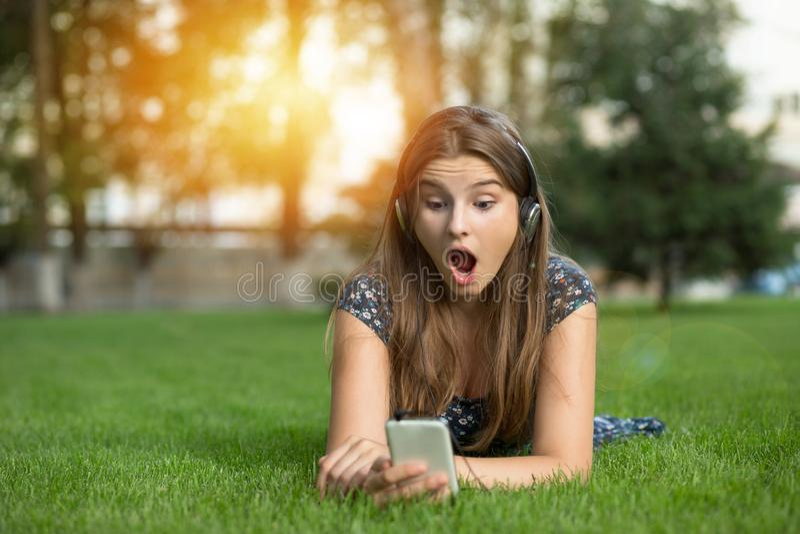 Shocked teenager looking at phone headphones on head reading shocking royalty free stock photos