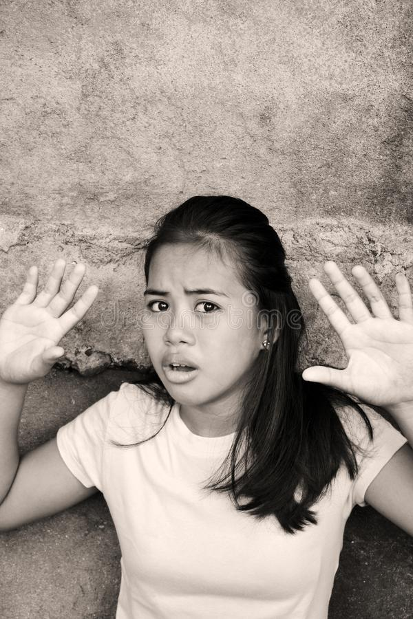 Shocked teenager screaming NO. Shocked Asian young lady leaning on a wall with the hands up in a poor area looking at something with fear stock photo