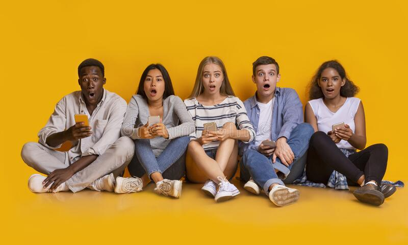 Shocked teenagers using phones, sitting on floor over yellow background. Shocking mobile app. Amazed teenagers using mobile phones, sitting on floor over yellow royalty free stock photos