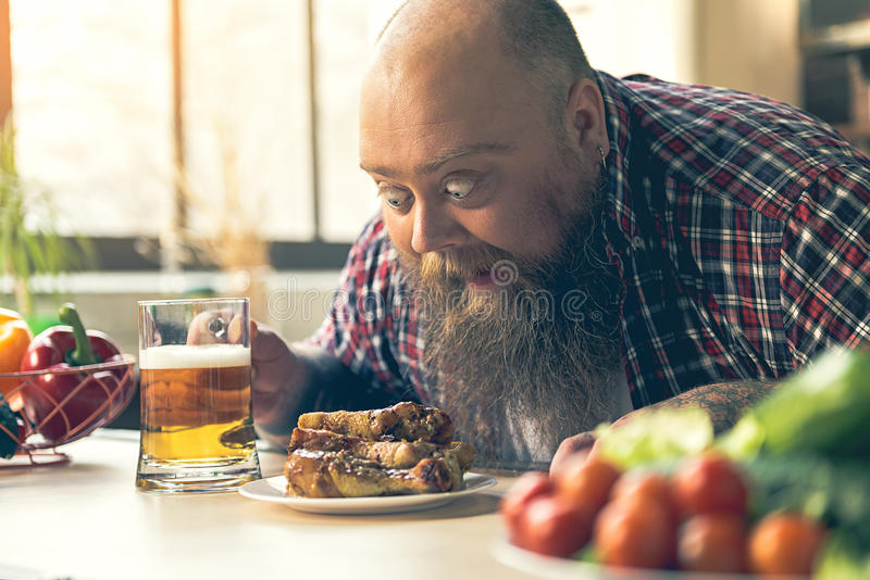Shocked thick guy looking at chicken legs royalty free stock photo