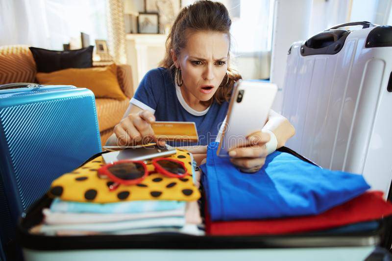 Shocked tourist woman with credit card paying for hotel room royalty free stock photography