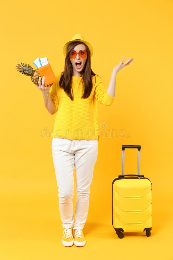 Shocked traveler tourist woman in hat holding passport tickets, fresh pineapple fruit isolated on yellow orange. Background. Passenger traveling abroad on stock image