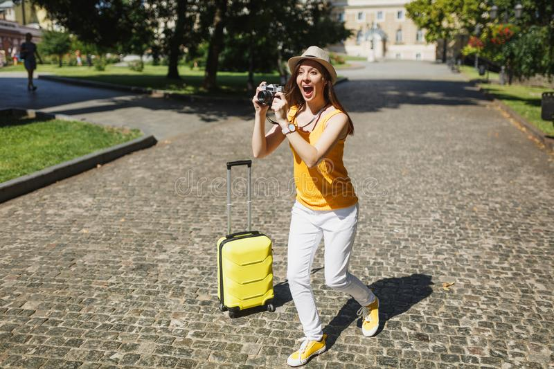 Shocked traveler tourist woman in yellow casual clothes with suitcase take pictures on retro vintage photo camera royalty free stock photos