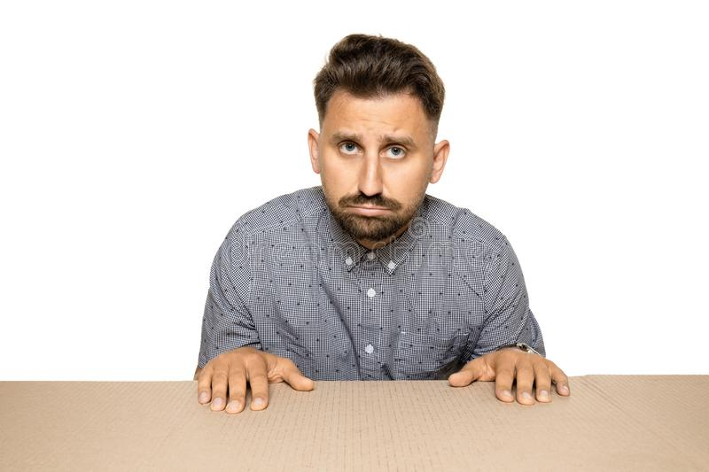 Shocked and upset man opening the biggest postal package. Sad and disappointed young male model on top of cardboard box looking inside. Gift, present, delivery royalty free stock photos