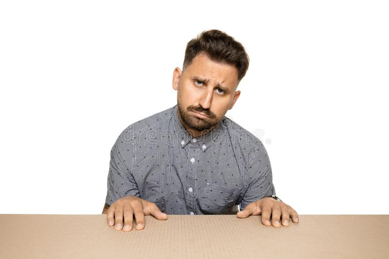 Shocked and upset man opening the biggest postal package. Sad and disappointed young male model on top of cardboard box looking inside. Gift, present, delivery royalty free stock photo