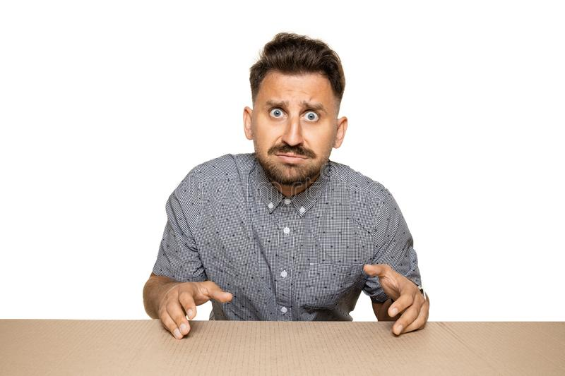 Shocked and upset man opening the biggest postal package. Sad and disappointed young male model on top of cardboard box looking inside. Gift, present, delivery royalty free stock image