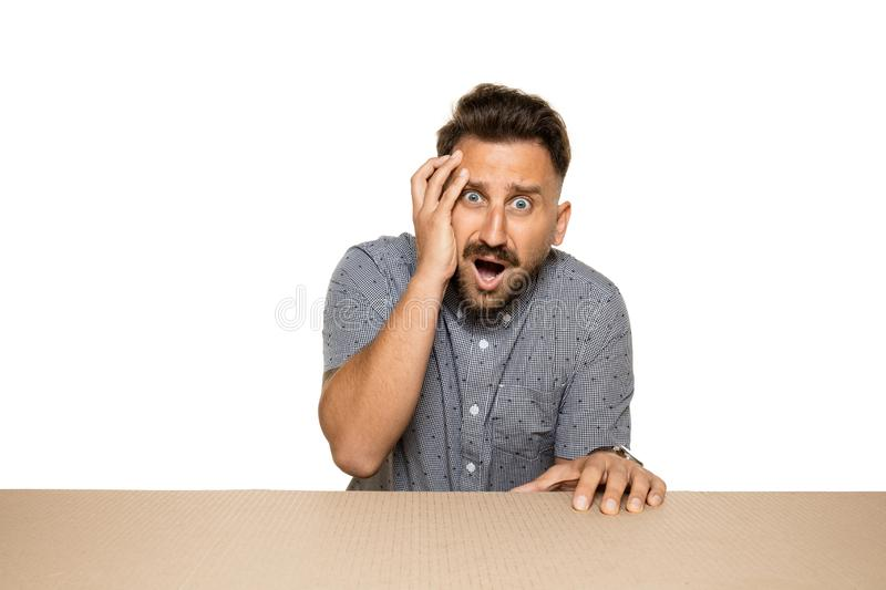 Shocked and upset man opening the biggest postal package. Sad and disappointed young male model on top of cardboard box looking inside. Gift, present, delivery royalty free stock images