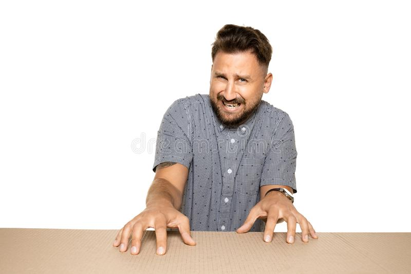 Shocked and upset man opening the biggest postal package. Sad and disappointed young male model on top of cardboard box looking inside. Gift, present, delivery stock images