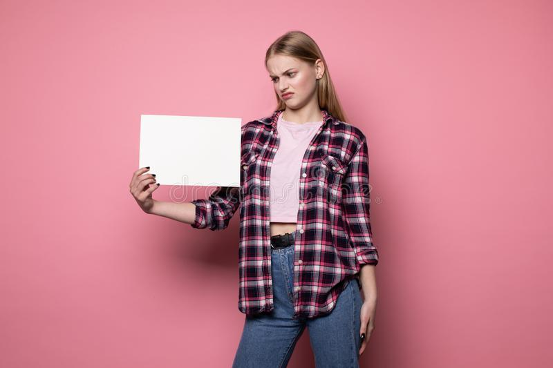 Shocked upset young woman in casual clothes, holding white empty blank for your text royalty free stock photography