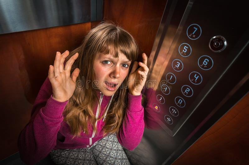 Shocked woman with claustrophobia in the moving elevator royalty free stock image