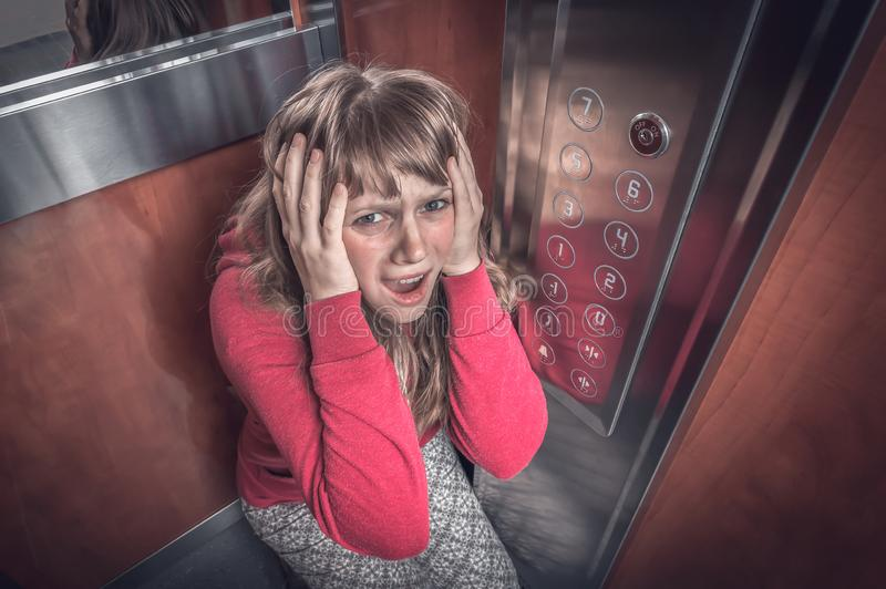 Shocked woman with claustrophobia in the moving elevator royalty free stock photography