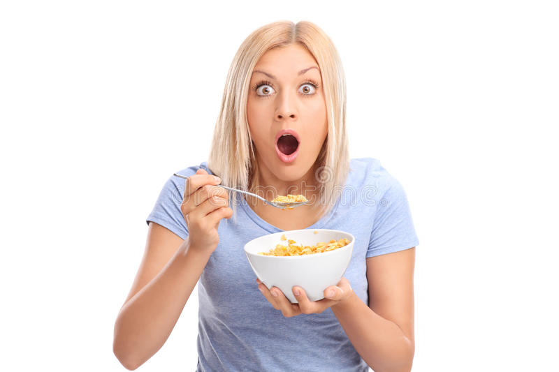 Shocked woman eating cereal from a bowl royalty free stock photos
